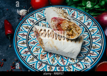 Doner kebab (shawarma or doner wrap). Grilled chicken on lavash (pita bread) with fresh vegetables - tomatoes, green salad, peppers. Old wooden backgr - Stock Photo