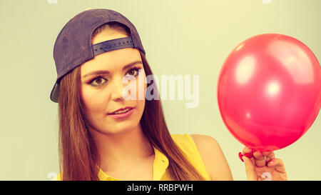 Teenage girl making funny silly faces. Young trendy woman in jeans cap holding red balloon. - Stock Photo