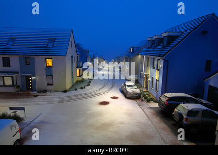 Looking down a road towards the sea with new snow falling and the cloud merging in with the sea on a winters evening in a quiete housing rural estate. - Stock Photo