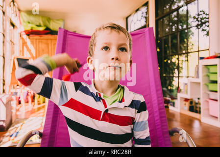 Boy throwing darts sitting in a pink chair. - Stock Photo