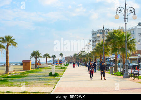 LARNACA, CYPRUS - FEBRUARY 19, 2019: People walking by Larnaca embankment. Larnaca  is a port city in Cyprus. Famous tourist destination - Stock Photo