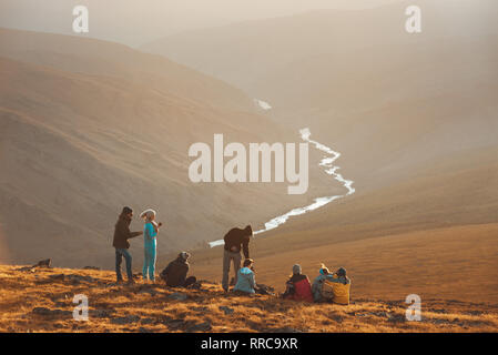 Big group of friends peoples relax on mountain top and looks at sunset - Stock Photo