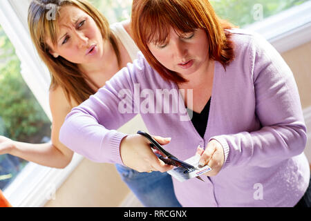 Mother cutting up her daughters credit card - Stock Photo