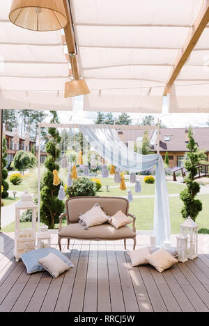 Cozy zone for a photoshoot on a terrace. A beautiful soft sofa, white wooden lamps and tassels made of thread - Stock Photo