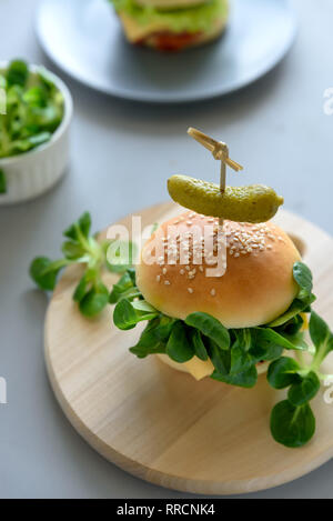 Tasty homemade vegan burgers with vegetables and greens on gray wooden background. Copy space - Stock Photo