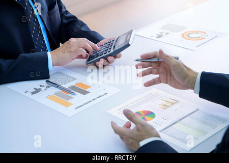 Two businessmen are deeply reviewing a financial reports for a return on investment or investment risk analysis on a white desk. Upper and lower right