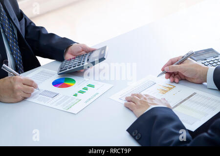 Two businessmen are deeply reviewing a financial reports for a return on investment or investment risk analysis on a white desk. Upper copy space incl