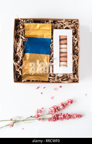 French macaroons with pack of coffee in brown craft paper gift box. Sweet macarons in giftbox and dried flowers on white table. Top view, flat lay. - Stock Photo
