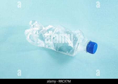 Plastic waste concept: discarded crumpled water bottle in blue background, detailed view. A thrown away single use plastic bottle depicting excessive