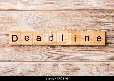 DEADLINE word written on wood block. DEADLINE text on wooden table for your desing, concept. - Stock Photo