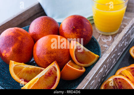 Blood Oranges Whole and Sliced on Plate and Tray with Glass of Orange Juice in Background - Stock Photo