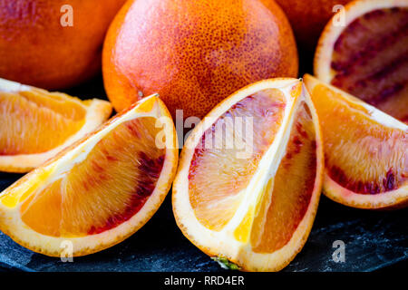Fresh Juicy Blood Oranges Whole and Sliced Close Up (macro) shallow depth of field - Stock Photo