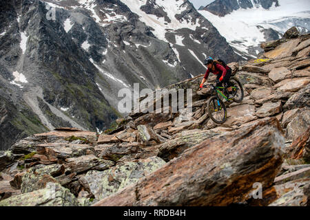 A woman rides a mountain bike on a rocky alpine trail in the Austrian ski resort of Sölden during the summer. - Stock Photo