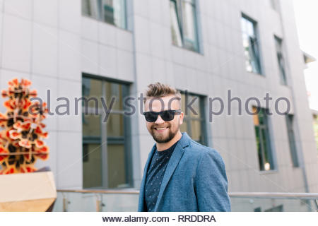 Portrait of handsome man in sunglasses walking on street on office building background. He wears T-shirt, jacket, beard. He is smiling to the camera. - Stock Photo