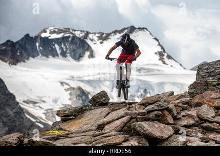 A man rides a mountain bike on a rocky alpine trail in the Austrian ski resort of Sölden in the summer. - Stock Photo