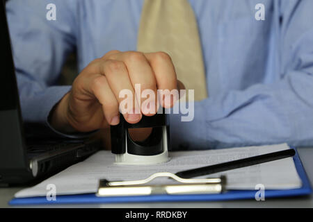 Man in the office puts a stamp on the documents. Concept of official, manager, permission, businessman, contract - Stock Photo
