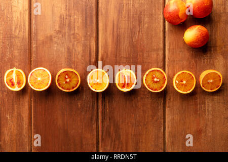 Organic blood oranges, whole and cut, shot from the top on a dark rustic background with copy space - Stock Photo