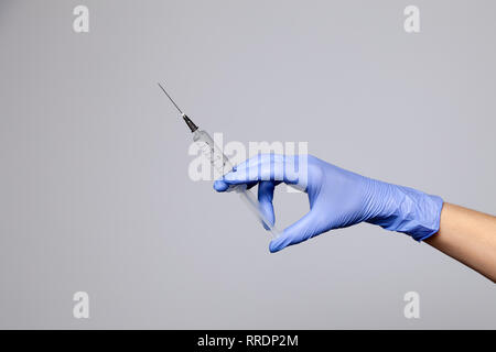 Closeup doctor's hand in rubber latex purple glove hold transparent syringe. Isolated on white background. Concept rejection of vaccinations, injectio - Stock Photo