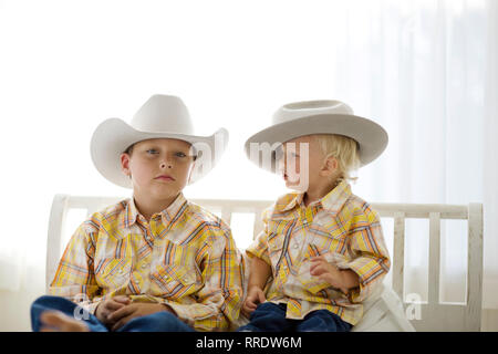 Portrait of a boy wearing a cowboy hat while sitting next to his younger brother. - Stock Photo