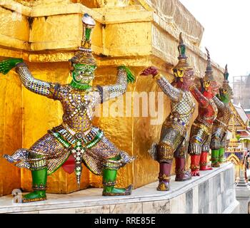 Demon Guardian Giant Statues Stand Around Pagoda and Liftting The Base of The Golden Pagoda at Wat Phra Kaew and The Grand Palace in Bangkok, Thailand - Stock Photo