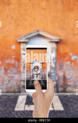 A man is making a photo of small drinking fountain with sculpture and stone decor in shabby painted wall, Rome on a mobile phone - Stock Photo