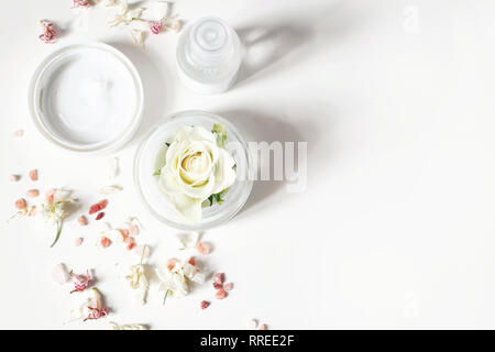 Styled beauty composition. Skin cream, shampoo bottle, dry flowers, rose and Himalayan salt. White table background. Organic cosmetics, spa concept. E - Stock Photo