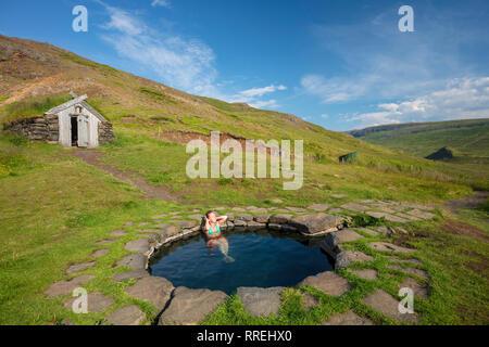 Woman bathing in Gudrunarlaug geothermal pool. Laugar, Saelingsdalur, west Iceland. - Stock Photo