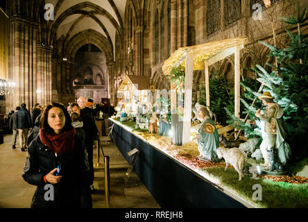 STRASBOURG, FRANCE - DEC 23, 2017: Nativity manger scene in the Notre-Dame de Strasbourg cathedral during winter holidays season representing the birth of Jesus - tourists admiring the statues - Stock Photo