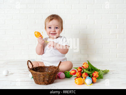 Cute toddler boy sitting with Easter eggs and tulips against white background - Stock Photo