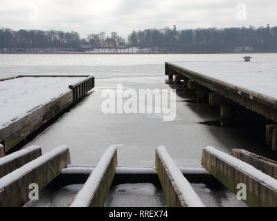 Perspective of Wooden Pier with Winter Snow and Frozen Lake - Stock Photo