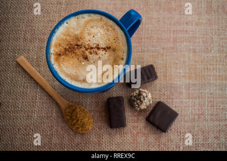 Coffee with milk and cinnamon in a blue cup with some chocolate - Stock Photo