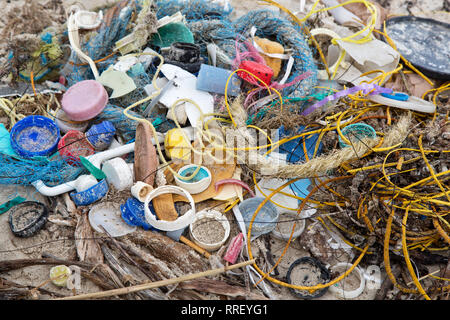 Trash collected on coastal beach. - Stock Photo