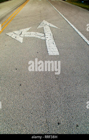 Looking down a stretch of empty road showing directional arrows painted on the road, pointing straight and left, they are old and cracked. - Stock Photo