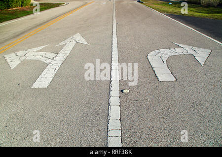 Looking down a stretch of empty road showing directional arrows painted on the road, pointing straight and left, and another pointing right, they are  - Stock Photo