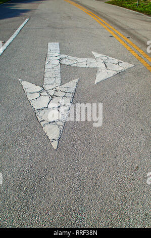 Looking down a stretch of empty road showing directional arrows painted on the road, pointing straight and for a turn, they are old and cracked. - Stock Photo
