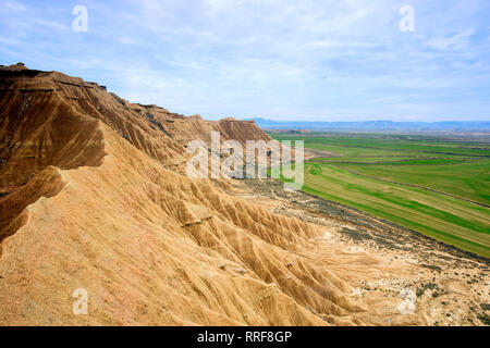 From above amazing view of stone mountains near green meadows and blue sky in Bardenas Reales, Navarra, Spain - Stock Photo