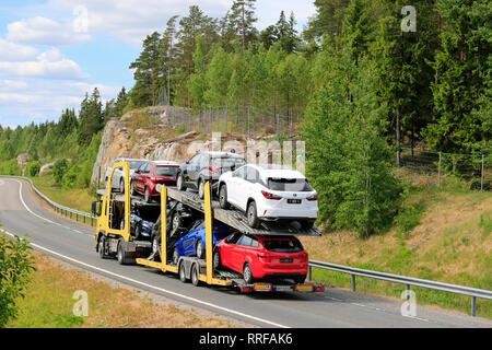 Salo, Finland - June 8, 2018: Yellow vehicle carrier truck with load of new cars driving on freeway ramp on sunny day of summer, rear view. - Stock Photo