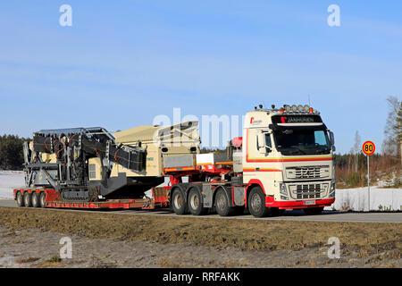 Salo, Finland - February 22, 2019: Volvo FH16 700 truck gooseneck trailer of Janhunen hauls Metso Lokotrack ST4.8 mobile screen along road in winter. - Stock Photo