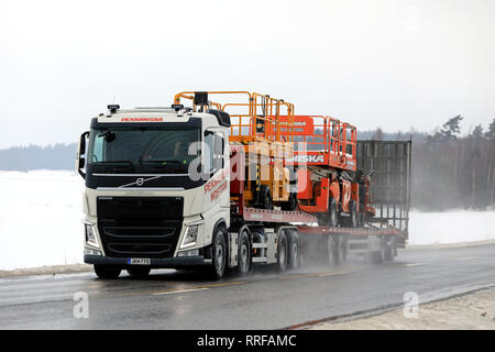 Salo, Finland - February 8, 2019: Volvo FH semi trailer hauls lifting equipment of Pekkaniska, a leading Finnish company renting platforms and cranes. - Stock Photo