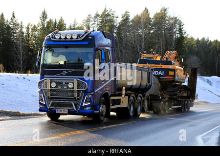 Salo, Finland - February 24, 2019: Blue Volvo FH truck of M. Toivonen Oy hauls Huyndai Robex LC300 tracked excavator on trailer along road in winter. - Stock Photo
