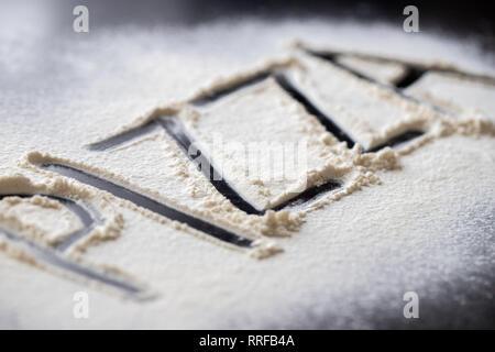 Pizza word written in flour on black table - Stock Photo