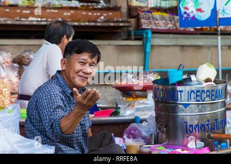 Damnoen Saduak, Thailand - August 29, 2018: Man selling coconut ice cream from a boat in Damnoen Saduak Floating Market, Ratchaburi, Thailand. - Stock Photo