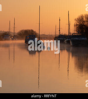 Wareham, Dorset, UK. 26th February 2019. UK Weather: The sky glows with orange and pink hues as the mist rises over the River Frome on a crisp, chilly February morning. A tranquil scene as sailing boats moored along the river bank are reflected in the calm water on the start of what is set to be another gloriously sunny day.  Credit: Celia McMahon/Alamy Live News - Stock Photo
