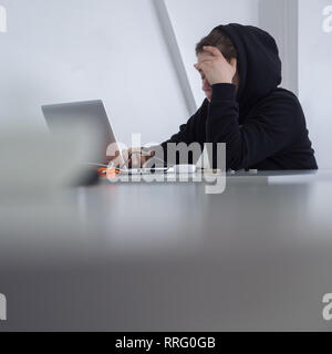 Student at desk. Working female. Woman qualified job. Searching for job. Girl in hoody sits at desk. Modern muslim woman. Refugee looking for job - Stock Photo