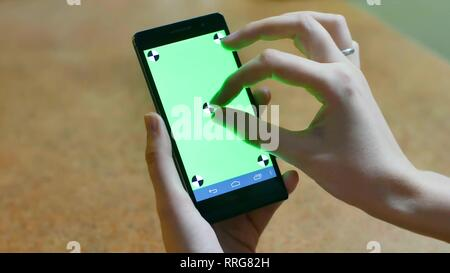Womans hands using a Smart phone Touchscreen CHROMA KEY Close-up , Fingers make gestures touching and swiping the screen of a modern smartphone. - Stock Photo