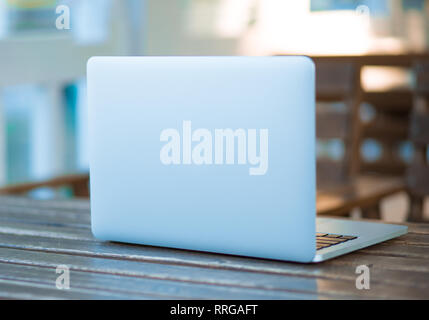Front view of a laptop on table in a coffee shop, balcony office on blured summer background. - Stock Photo