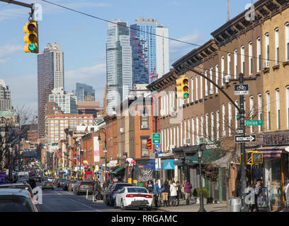 Looking north up Smith Street in the traditionally Italian Carroll Gardens neighborhood of Brooklyn, New York. Downtown Brooklyn shoots up in the background. - Stock Photo