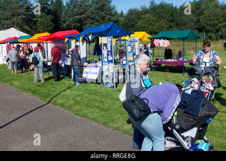Families and spectators are entertained by local stall and a boucy castle as they wait for the competitors to return.Lochaber Fort william Scottish Hi - Stock Photo