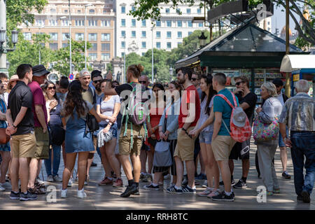 Tourists in the Plaça de Catalunya, a large square int the centre of Barcelona - Stock Photo