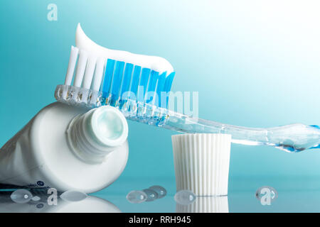 New toothbrush with toothpaste close-up in the bathroom on a mirror table with water drops on a blue background in the sunlight - Stock Photo
